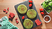 Raw green chicken and spinach burgers with spices on a stone plate in hard light, top view. Eating healthy concept, dinner idea for dieting, weight-loss-friendly foods, rustic style