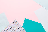 Paper geometric background in pink and mint green colors. Geometric shapes, minimalisctic backdrop with colored paper, frame, top view, copy space