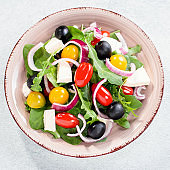 Greek salad closeup on concrete background. Top view of vegetable salad with feta cheese, arugula, cherry tomatoes and olives, vegetarian nutrition, healthy diet
