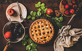 Flat-lay of whole apple and plum pie and tea setting