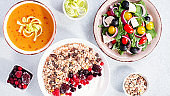 Carrot cream soup, Greek salad, granola bowl with yogurt on concrete table top with copy space. Assortment of dishes for diet, suitable for volumetrics diet and other nutrition strategies, top view