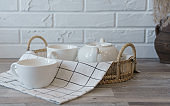 White ceramic Tea pot and cups on rattan tray on wooden counter