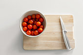 A bowl of cherry tomatoes on a cutting board. Cooking healthy and tasty food