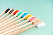 A set of Eco-friendly antibacterial toothbrushes made of bamboo wood on a light green background. Environmental care trends