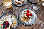 Sweet cakes with summer berries on a wooden table. Party, sweet table. Summer offer desserts in the restaurant.