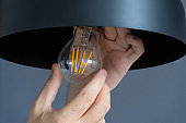 Close-up. A hand changes a light bulb in a stylish loft lamp. Spiral filament lamp. Modern interior decor.