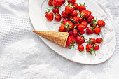 A plate of ripe juicy red strawberries and a waffle cone. Still life of summer delights