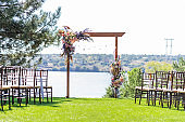 A beautiful venue for an open-air wedding ceremony. Wedding arch and rows of guest chairs on a green lawn overlooking the river