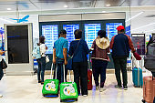 Passengers with suitcases at the airport look at the departure status information board