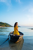 Beautiful brunette girl in a yellow dress sits in an old wooden boat overlooking a deserted tropical island. Romance at sea
