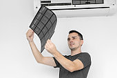 The guy cleans the filter of the home air conditioner from dust. The guy snayed a very dirty air conditioning filter. and examines it in his hands. Climate equipment care.