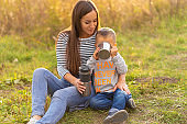 Happy family on autumn walk. Young beautiful mother with little son enjoy nature