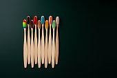 A set of Eco-friendly antibacterial toothbrushes made of bamboo wood on a dark green background. Environmental trends