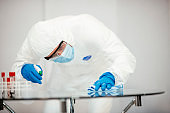 Covid-19 Wiping down surfaces. Man with gloves and disinfectant wipe sanitizing the desk to prevent germs and bacteria infections stock photo