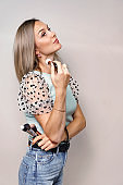 blond woman holding makeup brush and posing against grey background