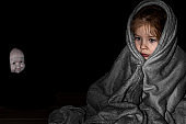 a little girl sitting in the dark wrapped in a blanket, in the background the blurred face of a scary doll. children's night fears