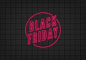 Black Friday neon sign on black tiles background. Concept of advertising for seasonal offer with glowing neon text.