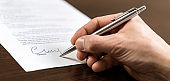 A businessman sits at an office Desk and signs a contract with a ballpoint pen