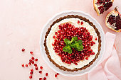 Homemade dessert chocolate tart with coconut cream and pomegranate and mint on a pink table background. Top view.