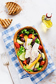 Greek salad in wooden plate on a white background. Traditional Greek dish. Selective focus. Top view.