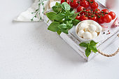 Mozzarella cheese balls, cherry tomatoes and green fresh organic basil. Ingredients for preparing Italian salad cuisine.