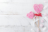 Group of festive various candies in form of  heart on white wooden background. Selective focus. Vintage Valentine card. Top view. Place for text.