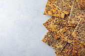 Abstract background of useful bread with sunflower seeds, flax and sesame seeds. Selective focus. Top view.