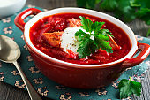Beetroot soup with meat, sour cream and parsley in a brown ceramic bowl on the old wooden background. Borsch- traditional dish of Ukrainian cuisine. Selective focus.