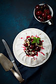 Homemade meringue cake Pavlova with whipped cream, fresh cherry and  sauce  on dark concrete texture background.Selective focus. Top view, space