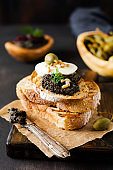 Sandwich with slice of mozzarella cheese and tapenade, caper on dark rustic table background. Traditional Provence dish. Selective focus.