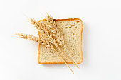 Toasted bread sliced into slices and ears of wheat on a white background. Top view, flat lay