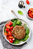 """Grilled steak of beef with cherry tomatoes and spinach, garlic, seasonings, peppers and onions. Pleskavitsa """"u2013 traditional Serbian dish. Top view."""