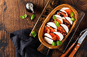 Caprese traditional italian salad in olive wooden bowl on old rustic background. Top view.