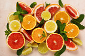 Orange, lemon, grapefruit, mandarin and lime on trendy pink stone or concrete table background. Citrus fruits. Top view, flat lay