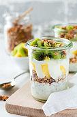 Yogurt granola parfait with mango,kiwi, tropical fruits nd hia seeds, layered dessert or breakfast. Selective focus.
