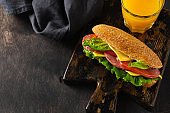 Healthy sandwiches with bran bread, cheese, lettuce, tomato and sliced salami and glass of freshly squeezed orange juice on rustic wooden stand. Breakfast concept. Top view.