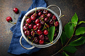 Fresh cherry in  iron bowl on a dark concrete background for a pie. Selective focus. Top view.