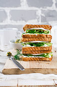 Sandwich for breakfast stuffed with slices of cucumber, curd cheese, ham and dill on old wooden background.