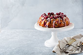 Lemon bundt-cake with raspberries on a light background. Selective focus.