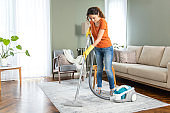 Young housewife cleaning house with vacuum cleaner