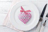 Vintage decorative heart-shaped decoration on a wooden stand on white background. Selective focus. Vintage Valentine card. Top view. Place for text.