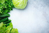 Concept of fresh green lettuce, cabbage, cucumber, dill, lime on a light background. Selective focus.Healthy raw Organic  food.Top view. Copy space.
