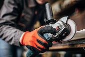 Manual worker grinding in workshop