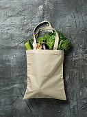 Cotton bag with vegetables on gray background