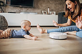 Beautiful mother and her baby boy playing while robotic vacuum cleaner cleaning