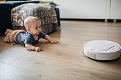 Baby boy playing at home and discovering robotic vaccum cleaner