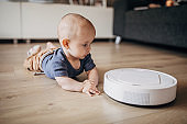 Baby boy playing in living room and discovering robotic vaccum cleaner