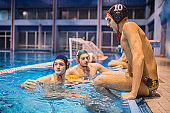 Young men water polo players on the relaxing edge of the pool