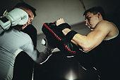 Men kick boxers sparring together on kick box training