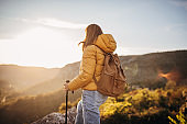 One woman with backpack hiking in the mountains and catching the sunset